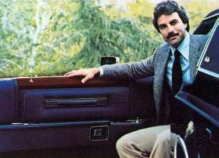 "Door panels are covered in luxury cloth and feature Ebony woodtone applique accents. The model is Tom Selleck (""Magnum, P.I."")"
